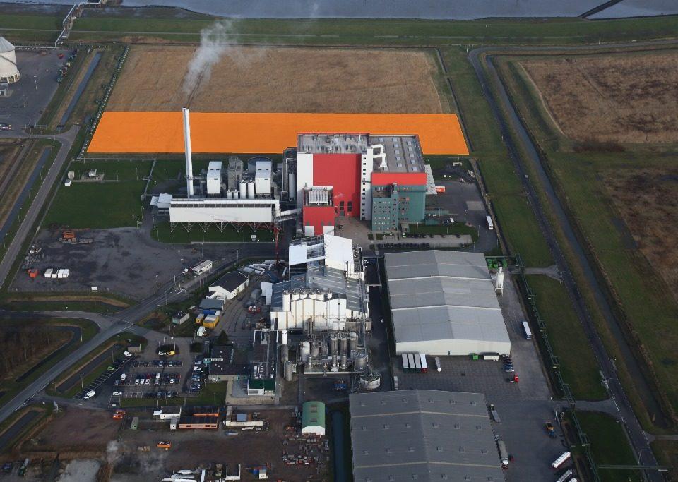 De afvalenergiecentrale EEW Energy from Waste (rode fabriek) met daarachter het uitbreidingsgebied (oranje vlak)